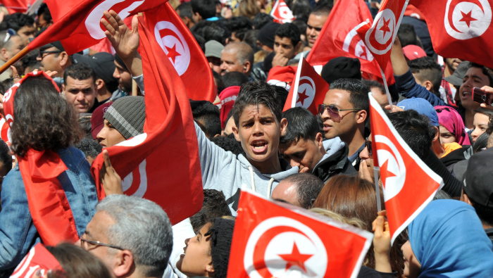 (FILES) A photo taken on March 29, 2015 shows Tunisians waving their national flag and chant slogans during a march against extremism outside Tunis' Bardo Museum. Tunisian mediators of the socalled National Dialogue Quartet (Tunisian General Labour Union UGTT, Tunisian Confederation of Industry, Trade and Handicrafts UTICA, Tunisian Human Rights League LTDH and Tunisian Order of Lawyers) won the 2015 Nobel Peace Prize, for helping to create the only democracy to emerge from the Arab Spring, at a time when the country is under threat from Islamist violence, the Norwegian Nobel Commitee announced on October 9, 2015   AFP PHOTO / FETHI BELAID        (Photo credit should read FETHI BELAID/AFP/Getty Images)