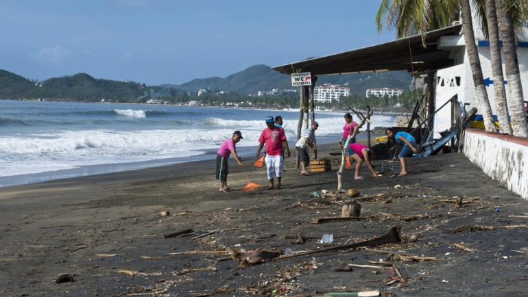 Locals clean debris at a beach restaurant in the outskirts of Manzanillo, state of Colima, after Hurricane Patricia hit the shore of neighbouring Jalisco state, on October 24, 2015. Record-breaking Hurricane Patricia weakened to a tropical storm over north-central Mexico on Saturday, dumping heavy rain that triggered flooding and landslides but so far causing less damage than feared.   AFP PHOTO/OMAR TORRES        (Photo credit should read OMAR TORRES/AFP/Getty Images)